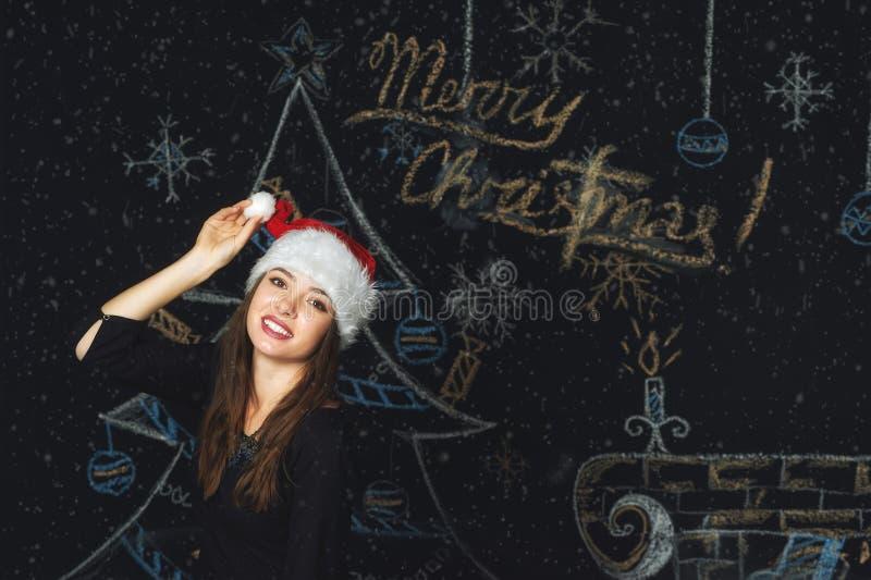 Stående av en ung kvinna i ett lock av Santa Claus på julbakgrund arkivbild