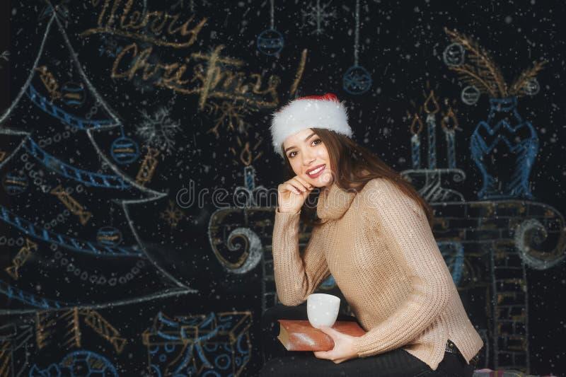 Stående av en ung kvinna i ett lock av Santa Claus på julbakgrund royaltyfria bilder