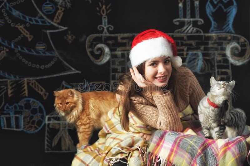 Stående av en ung kvinna i ett lock av Santa Claus på julbakgrund arkivfoton