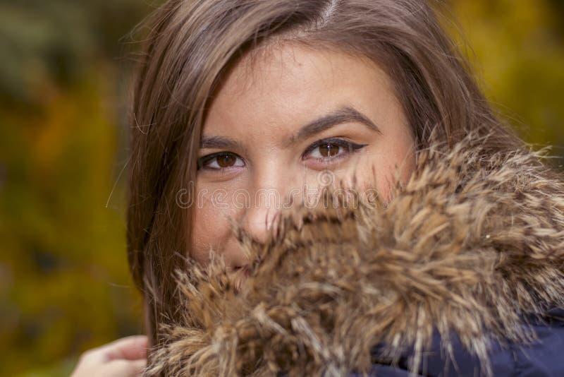 Stående av en ung kvinna i ett omslag med päls arkivbild