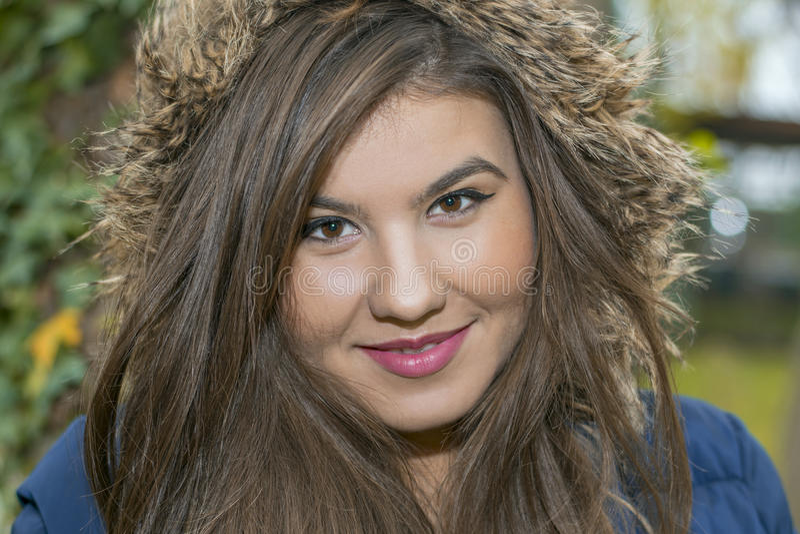 Stående av en ung kvinna i ett omslag med päls fotografering för bildbyråer