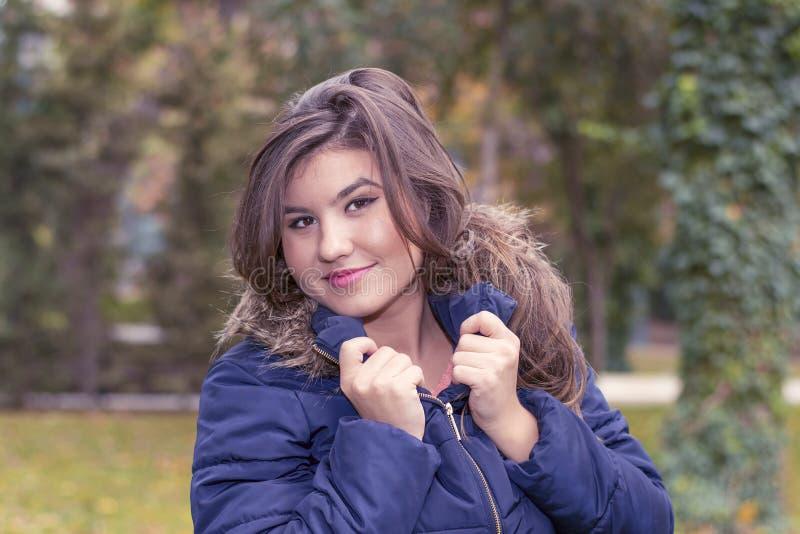 Stående av en ung kvinna i ett omslag med päls arkivfoto