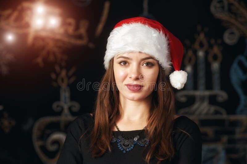 Stående av en ung kvinna i jultomtenhatt royaltyfri bild