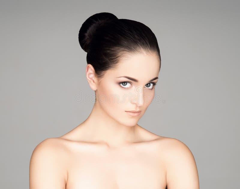 Stående av en ung kvinna i makeup på grå färger royaltyfri bild