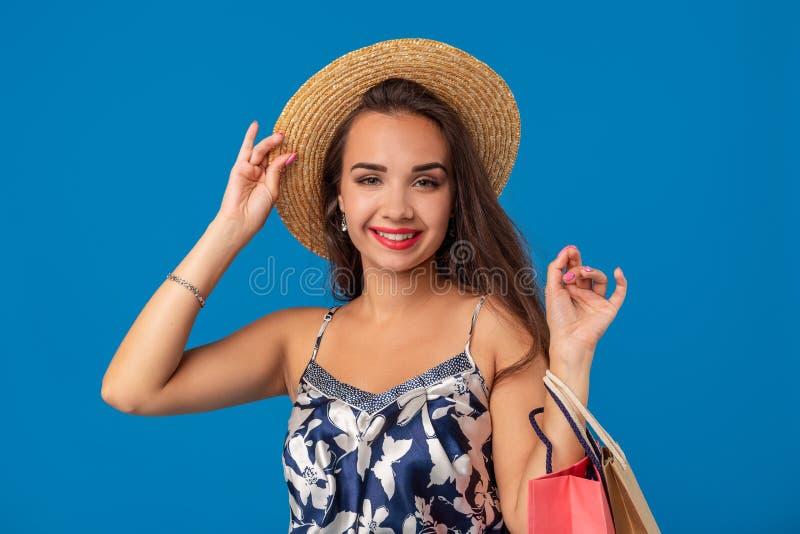 Stående av en ung kvinna i påsar för shopping för sommarhatt hållande och att se kameran som isoleras över blå bakgrund royaltyfri foto