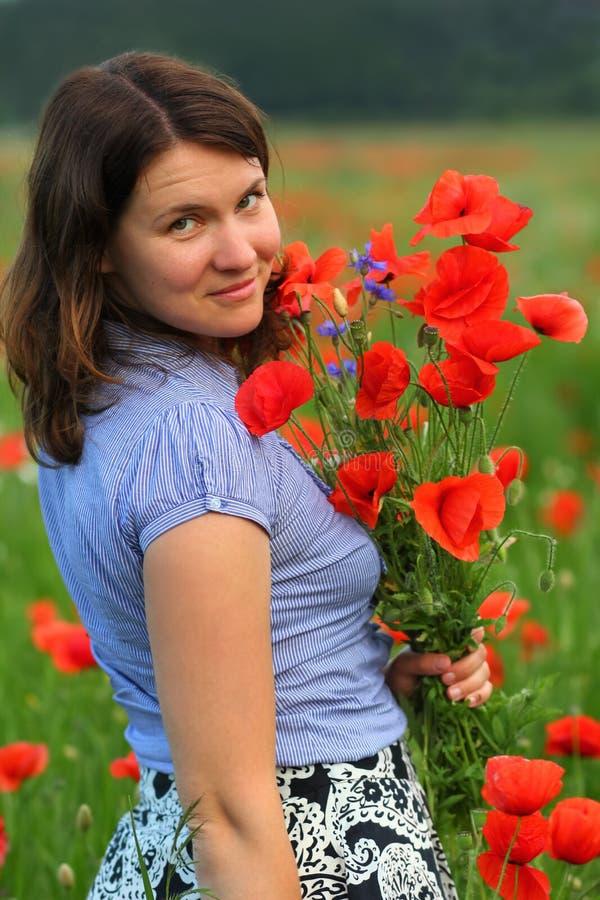 Stående av en ung kvinna i sommarfältet av att blomma vallmo som poserar med en bukett royaltyfri foto