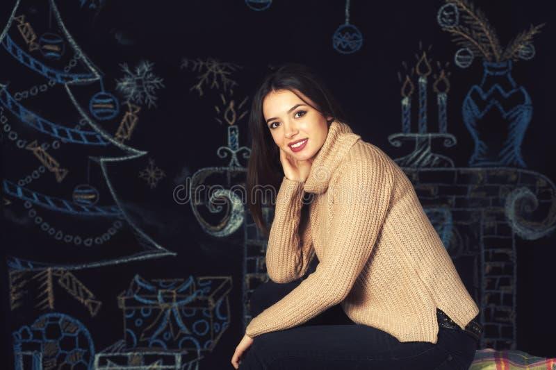 Stående av en ung kvinna i en varm tröja på en mörk bakgrund fotografering för bildbyråer