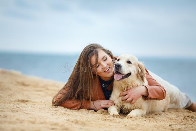 Stående av en ung kvinna med en hund på stranden arkivbilder