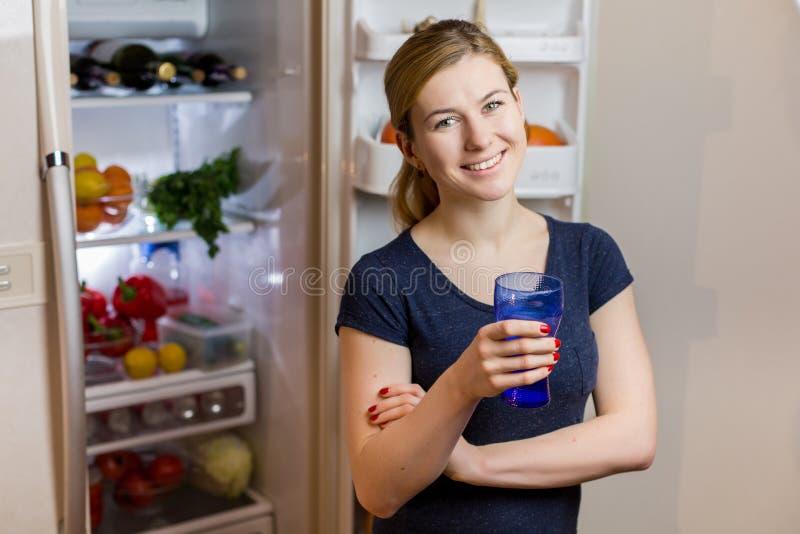 Stående av en ung kvinna med exponeringsglas av vatten framme av kylskåpet mycket av mat arkivbilder