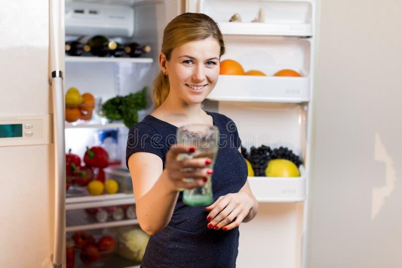 Stående av en ung kvinna med exponeringsglas av vatten framme av kylskåpet mycket av mat arkivbild