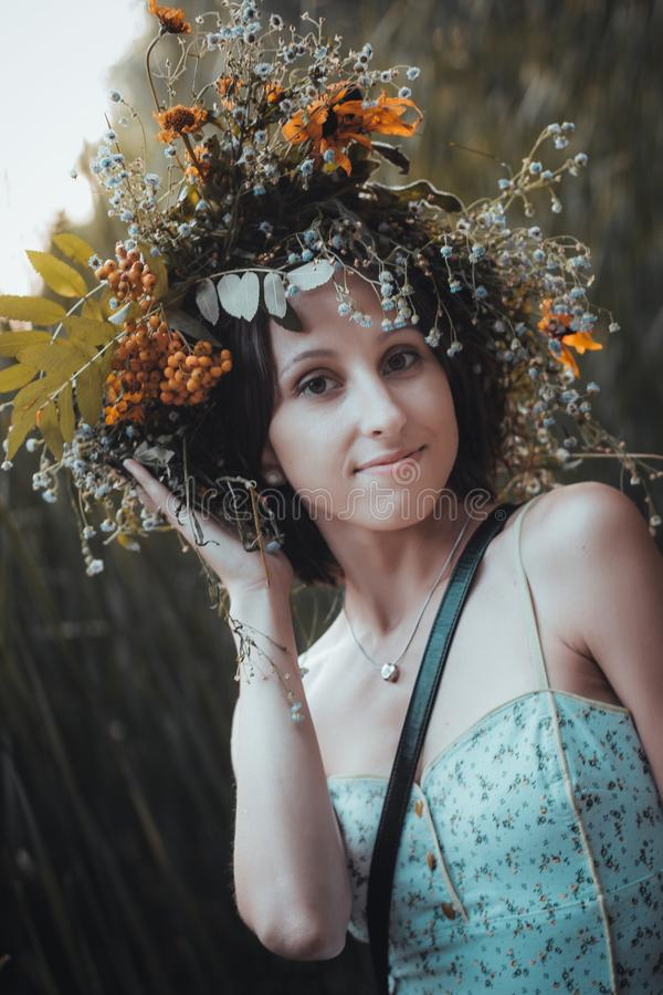 Stående av en ung kvinna med en krans av blommor på hennes huvud arkivfoto