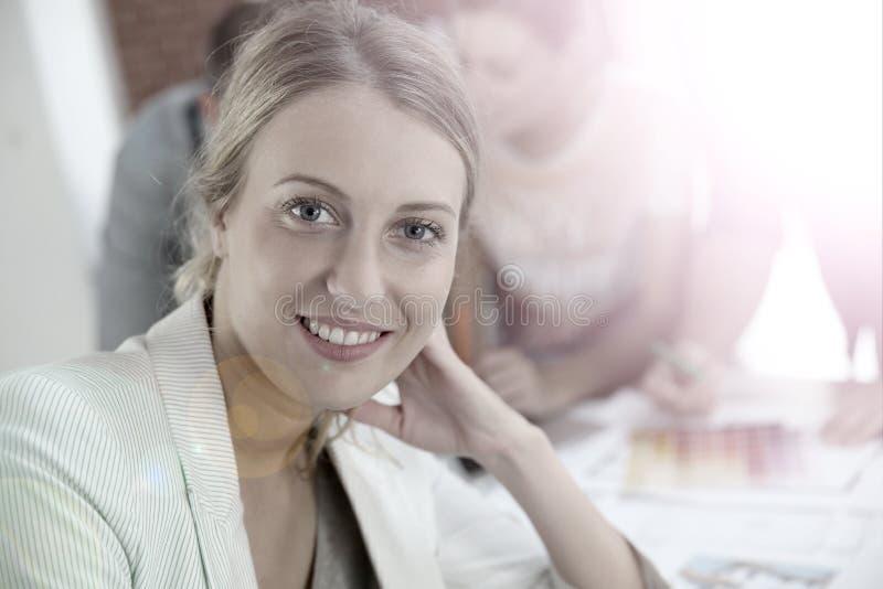 Stående av en ung kvinna på kontoret med kollegor i baksidan royaltyfri fotografi