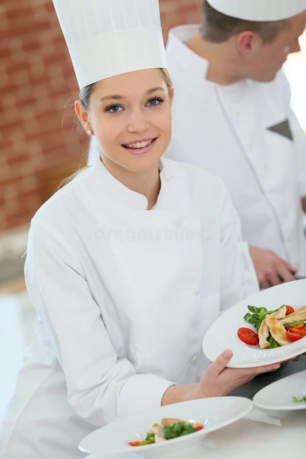 Stående av en ung kvinna på matlagninggrupp royaltyfri foto