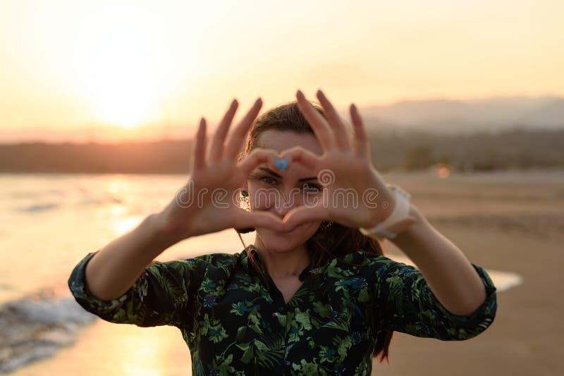 Stående av en ung kvinna på stranden på den röda solnedgången, hjärta av fingrar, meddelande av förälskelse arkivfoto