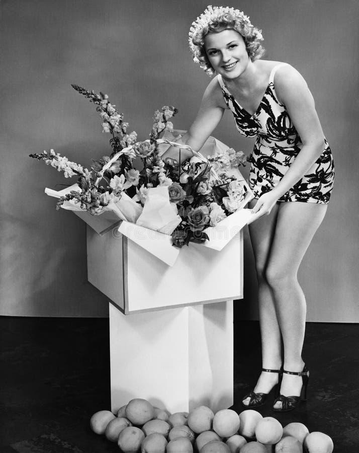 Stående av en ung kvinna som öppnar en gåva och le (alla visade personer inte är längre uppehälle, och inget gods finns Supplie arkivfoto