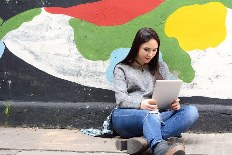 Stående av en ung kvinna som använder hennes minnestavla arkivbild