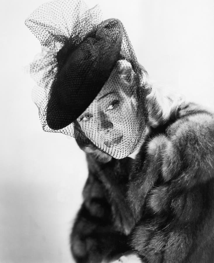 Stående av en ung kvinna som bär en päls och en hatt med en skyla (alla visade personer inte är längre uppehälle, och inget gods  fotografering för bildbyråer