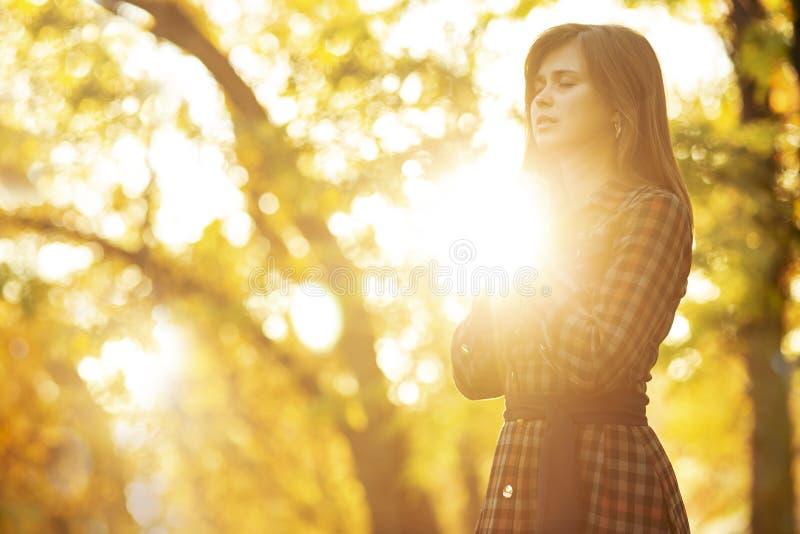 Stående av en ung kvinna som ber i natur, flickatackguden med hennes händer vikta på hennes haka, begreppet av religionen arkivbilder