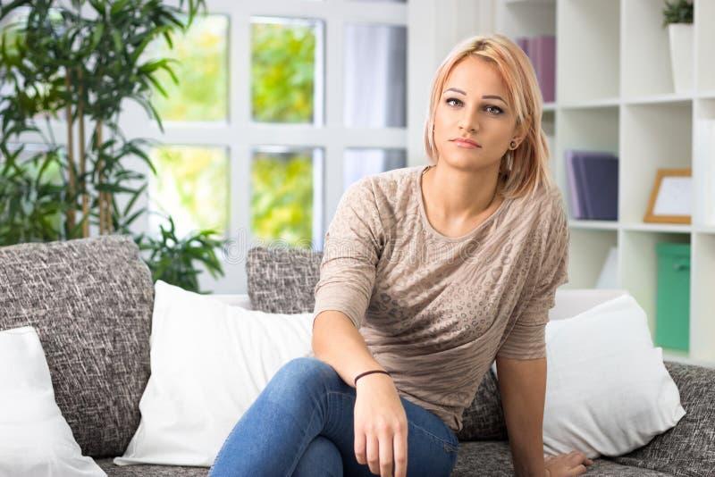 Stående av en ung kvinna som hemma kopplar av på soffan arkivbild