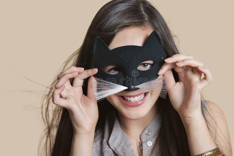 Stående av en ung kvinna som imiterar som katt, medan se till och med ögonmaskering över kulör bakgrund arkivfoton