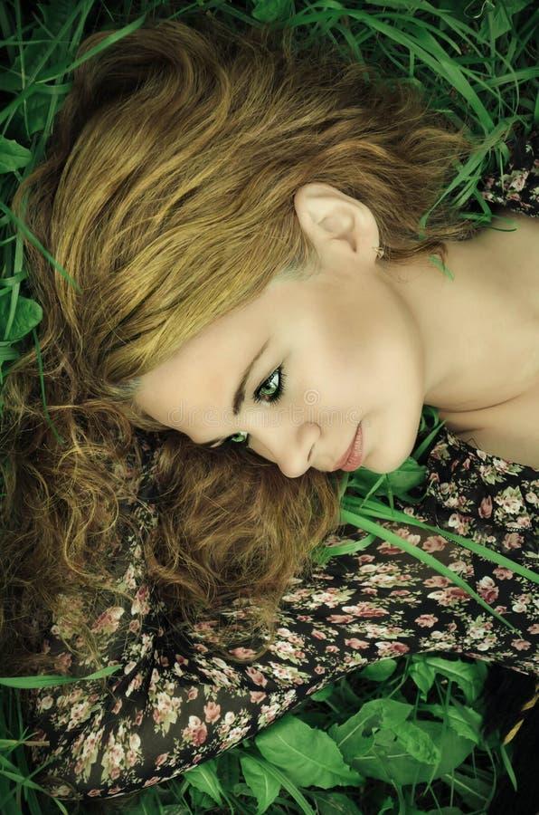 Stående av en ung kvinna som kopplar av på gräs royaltyfria bilder