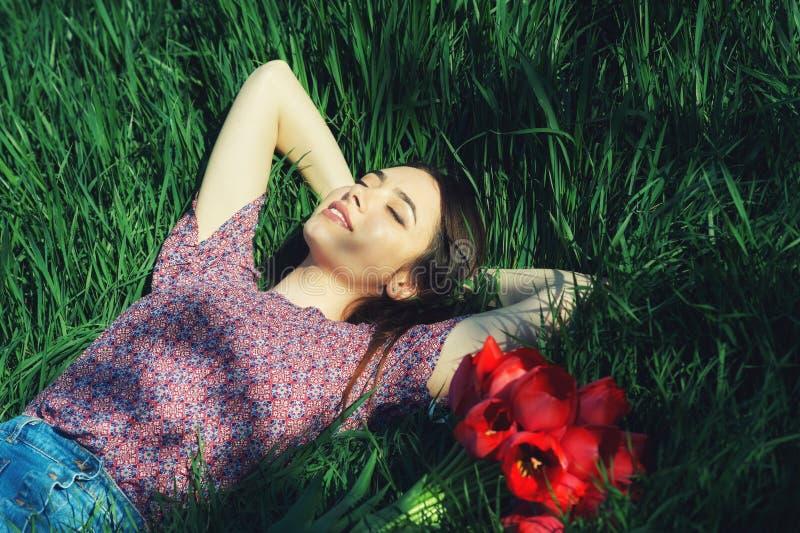 Stående av en ung kvinna som ligger på gräset fotografering för bildbyråer