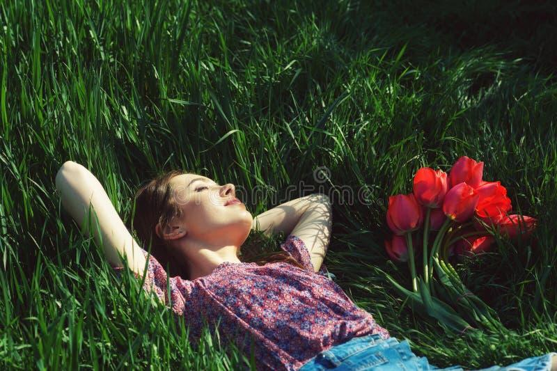 Stående av en ung kvinna som ligger på gräset arkivfoto