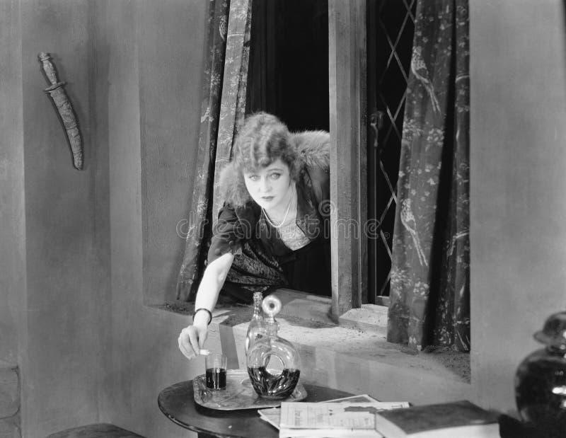 Stående av en ung kvinna som når till och med ett fönster och ett hällande gift in i ett exponeringsglas (alla visade personer in royaltyfri bild