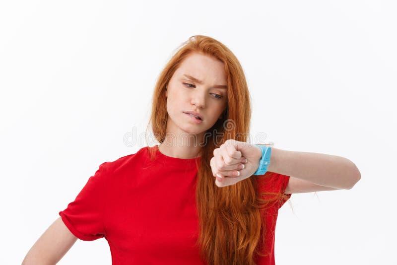 Stående av en ung kvinna som pekar fingret på armbandsuret som isoleras på en vit bakgrund royaltyfria bilder