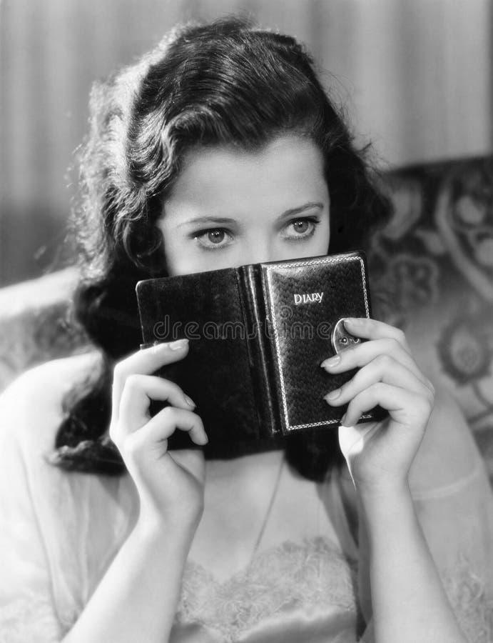 Stående av en ung kvinna som rymmer en dagbok och tänka (alla visade personer inte är längre uppehälle, och inget gods finns leve arkivbilder
