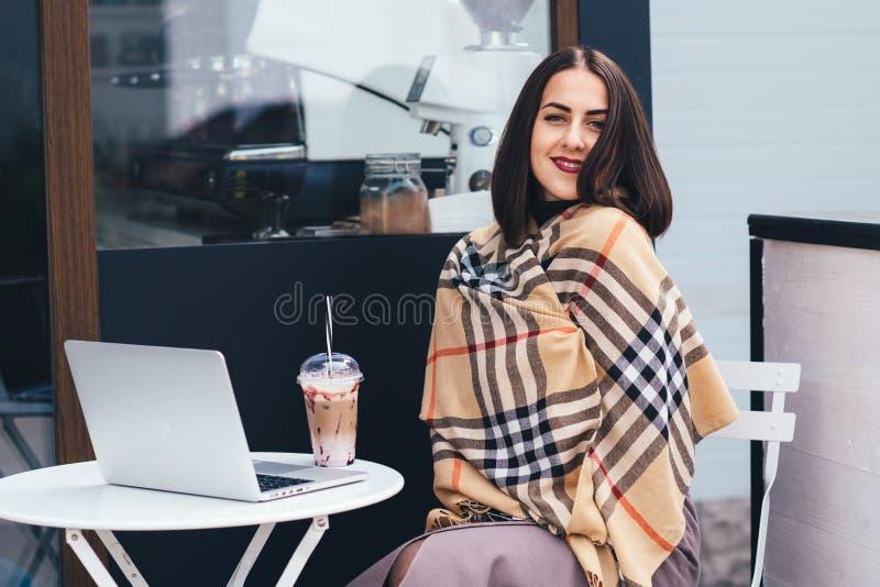 Stående av en ung kvinna som rymmer hennes bärbar datordator, medan sitta på en stol royaltyfri fotografi