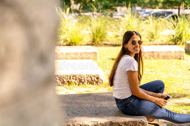 Stående av en ung kvinna som sitter på ett konkret kvarter royaltyfri fotografi