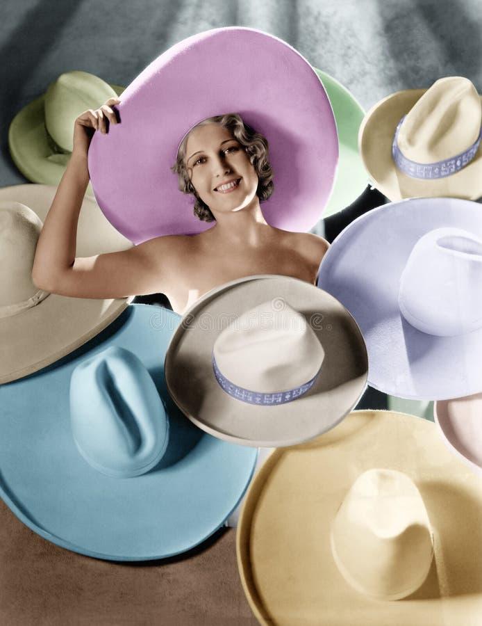 Stående av en ung kvinna som täckas med hattar (alla visade personer inte är längre uppehälle, och inget gods finns Leverantörgar arkivfoto