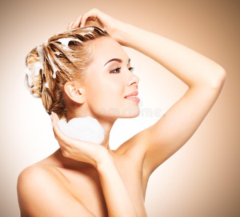Stående av en ung kvinna som tvättar hennes hår royaltyfria bilder