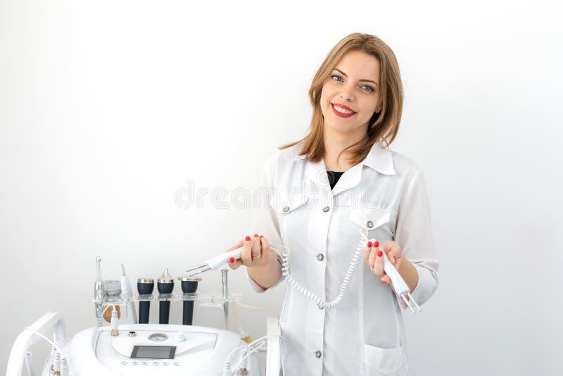 Stående av en ung le härlig flicka av en yrkesmässig kosmetolog på arbetsplatsen i ett vitt rent kontor arkivfoto