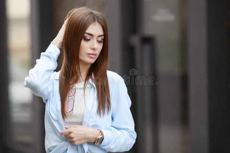 St?ende av en ung le h?rlig orientalisk kvinna med l?ngt m?rkt h?r Livsstilbild av en modell b?rande vit T arkivbild