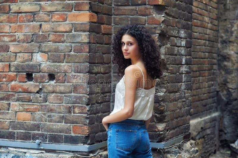 Stående av en ung lockig flicka i staden arkivfoto