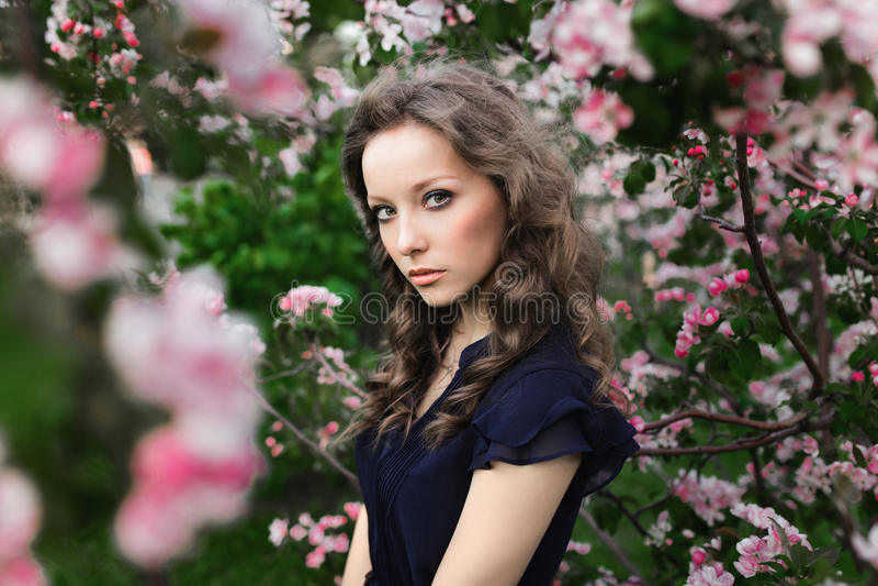 Stående av en ung lockig-haired flicka i ett blått klänninganseende bland ett blomstra äppleträd arkivbild
