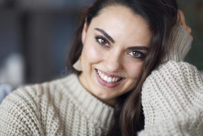 St?ende av en ung lycklig h?rlig kvinna i varma kl?der hemma arkivbilder
