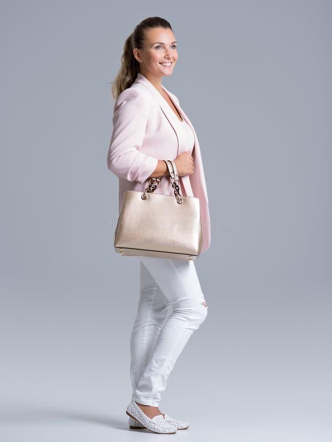 Stående av en ung lycklig kvinna med handväskan royaltyfri fotografi