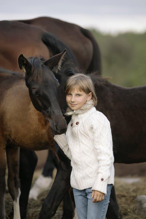 Stående av en ung lycklig liten flicka i den vit tröjan och jeans med fölet livsstil royaltyfria bilder