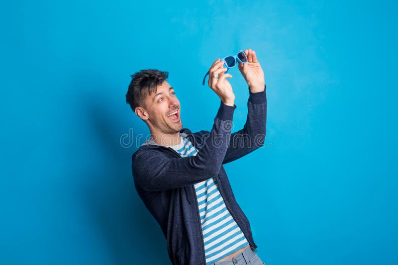 Stående av en ung lycklig man med solglasögon i en studio på en blå bakgrund royaltyfria bilder