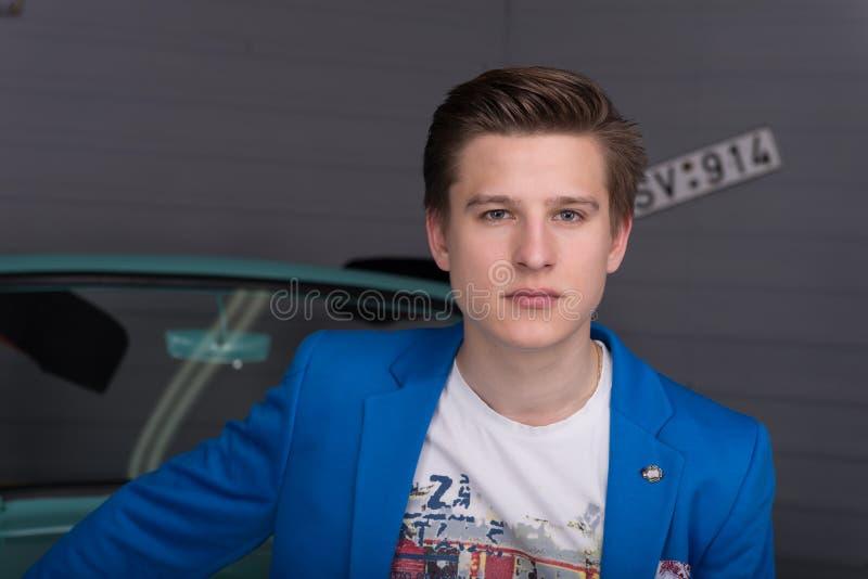 Stående av en ung man i bilgaraget royaltyfri bild