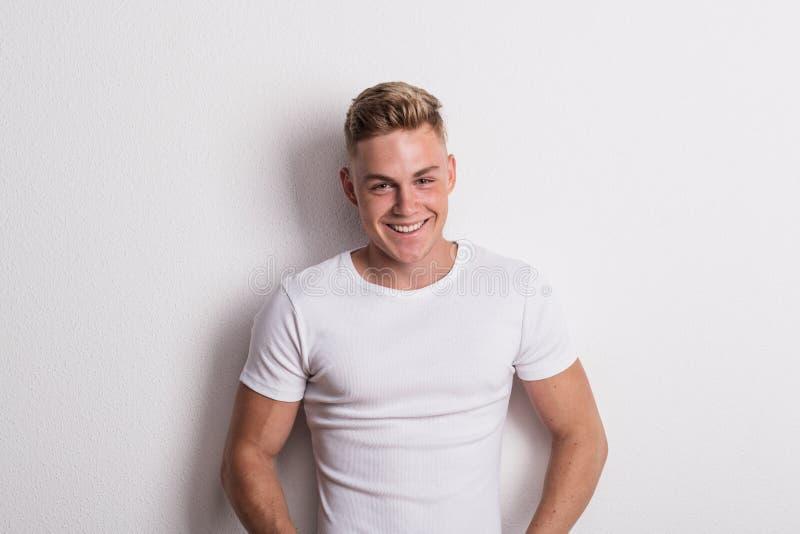 Stående av en ung man i den vita T-tröja i en studio som lutar mot väggen royaltyfria foton