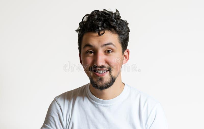 Stående av en ung man med att le för hänglsen En lycklig ung man med h?nglsen p? en vit bakgrund arkivbilder