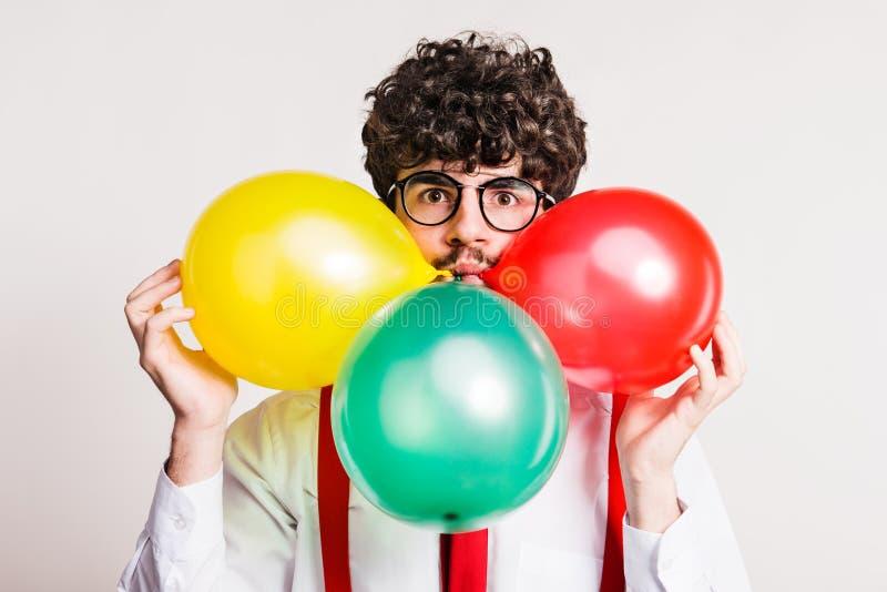 Stående av en ung man med ballonger i en studio arkivbild