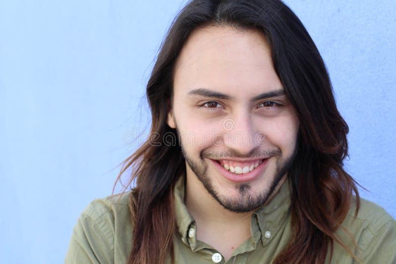 Stående av en ung man med den kalla långa frisyren som ser kameran På blå bakgrund arkivfoto