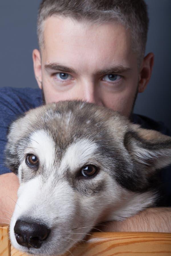 Stående av en ung man med en hund arkivbild