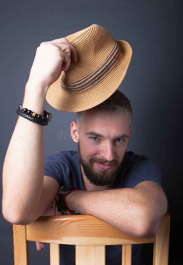Stående av en ung man med ett skägg och en hatt fotografering för bildbyråer