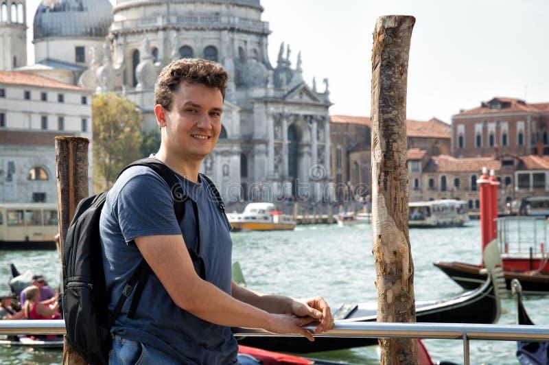 Stående av en ung man på den Grand Canal spårvagnstationen Basilika av Santa Maria della Salute på bakgrunden royaltyfri foto